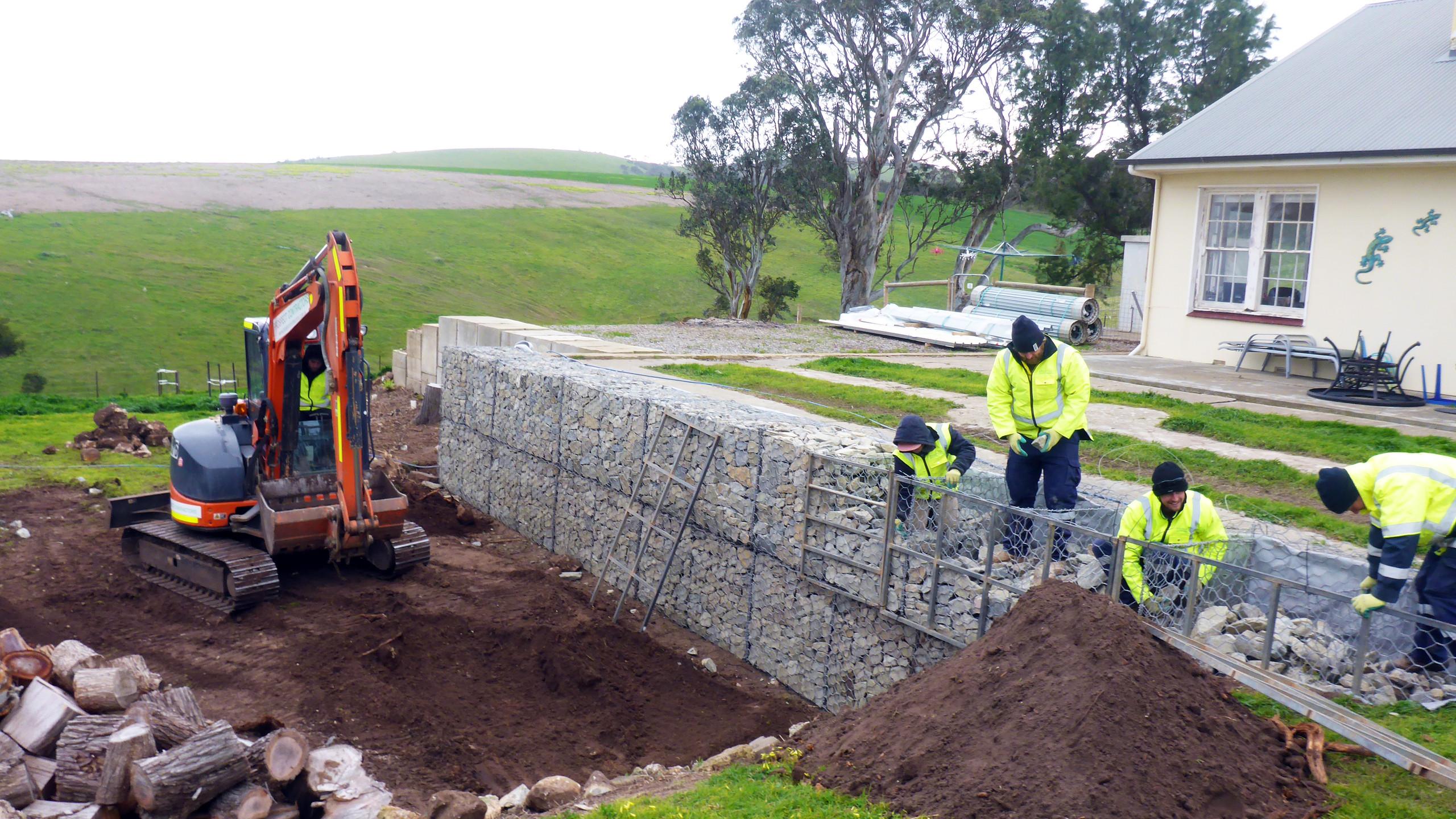 Hand filling a Gabion wall
