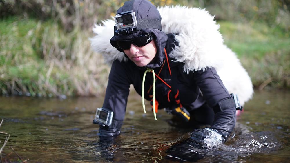 Miranda Whall crawling with sheep fleece through river