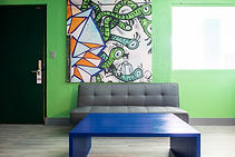 Living room of hotel room with green wall and art with grey couch and blue coffee table on hardwood.
