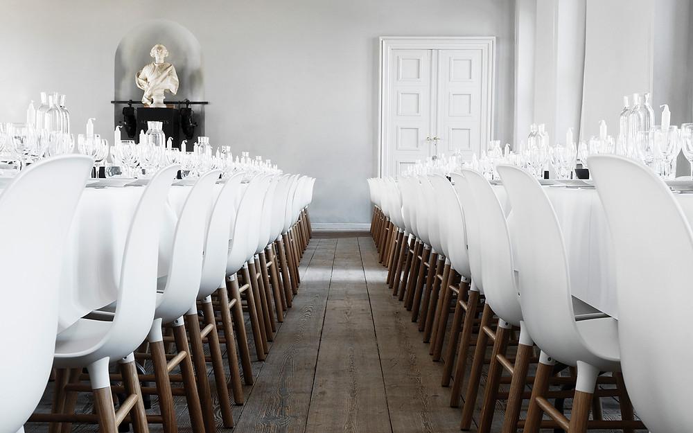 Form toolid valge plastikkattega ja suitsutamme jalaga Kopenhageni Charolottenborgi kunstimuuseumi pidusaalis.