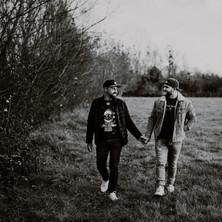 Photographe à Troyes, séance photo de couple qui se tient la main dans un champ en noir et blanc