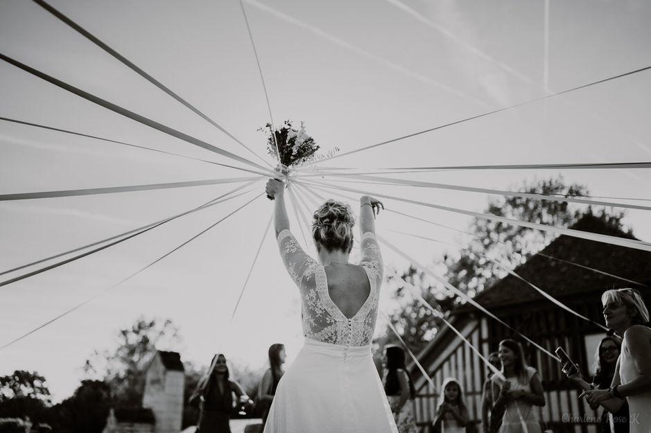 Mariée qui fait le jeu du ruban avec son bouquet de fleurs au Domaine de Vermoise