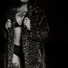 Photographe à Troyes, séance photo boudoir de femme tatouée avec fausse fourrure léopard en noir et blanc