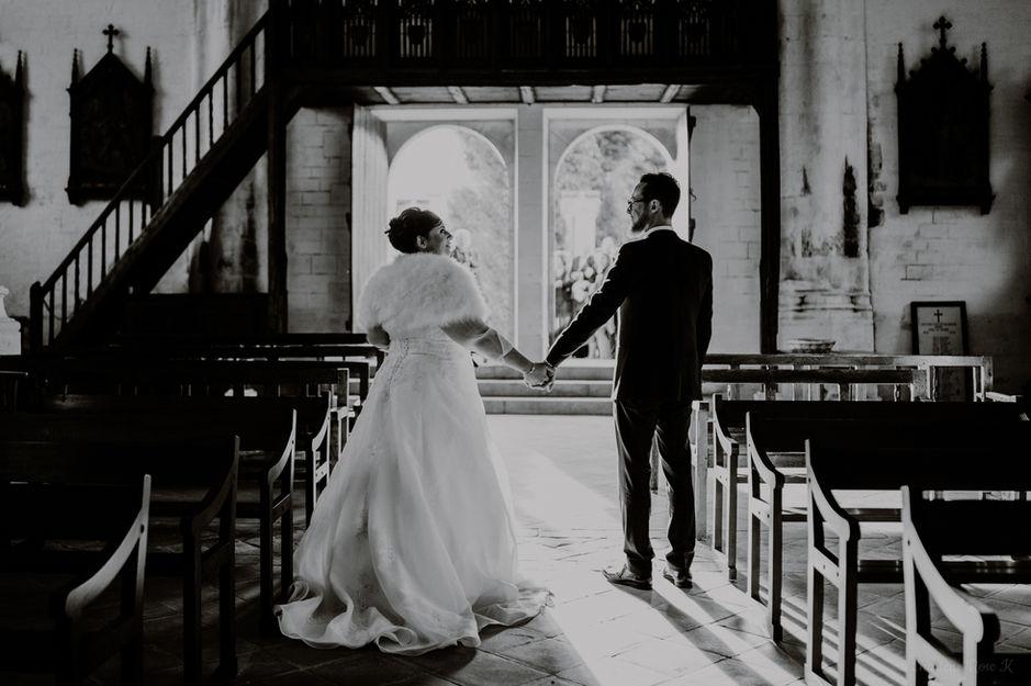 Couple de mariés qui forme un coeur à la sortie de l'église