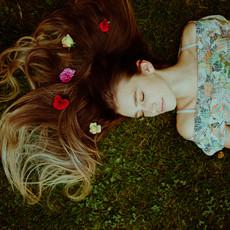 Photographe à Troyes, Portrait de femme allongée dans l'herbe avec fleurs dans les cheveux