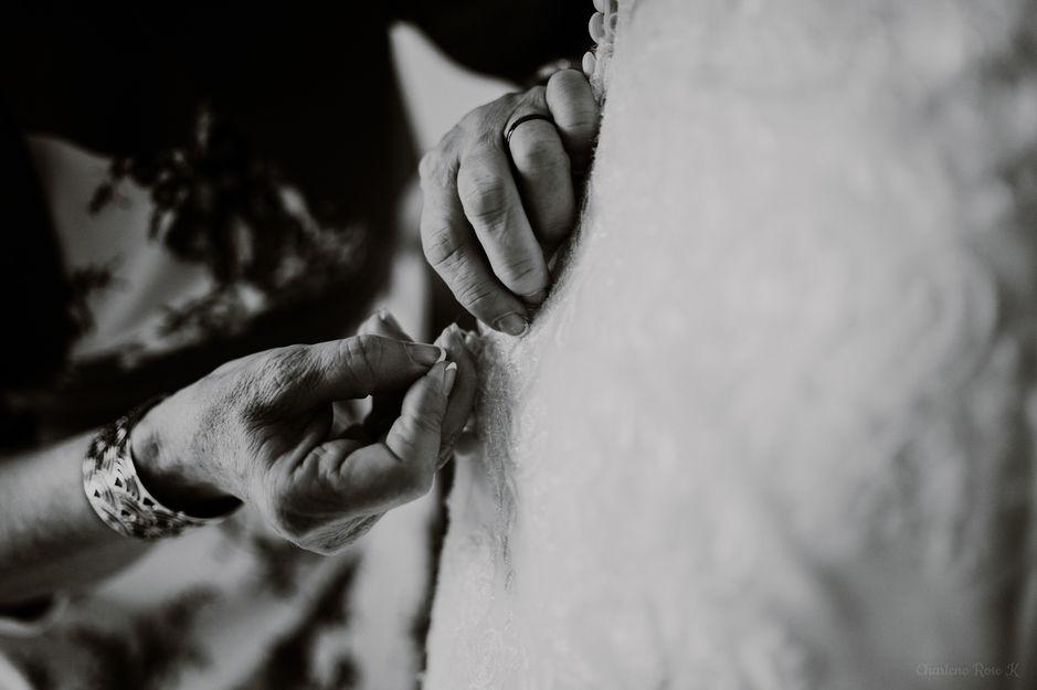 Préparatifs de la mariée, la maman boutonne la robe