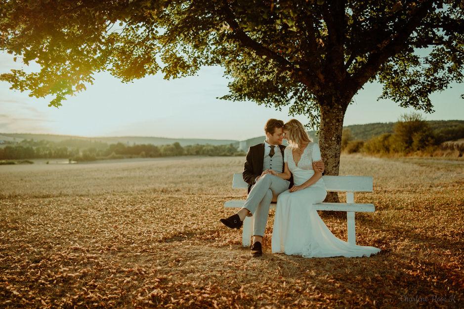 Couple de mariés assis sur un banc au coucher du soleil au Domaine de Rennepont en Champagne