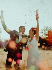 Mariés amoureux qui lancent des confettis colorés