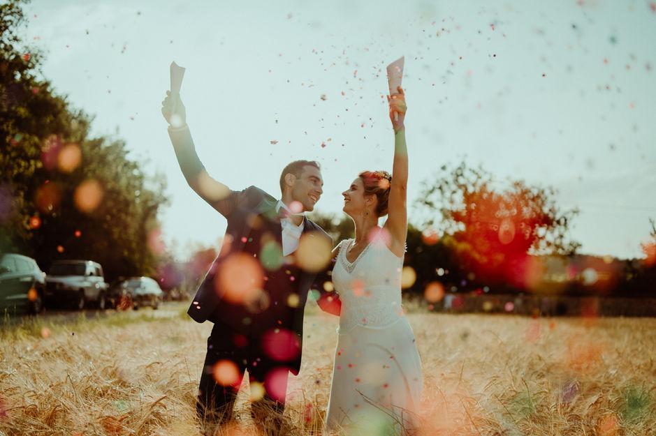Couple de mariés heureux qui lancent des confettis