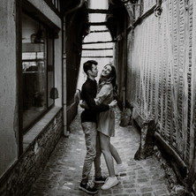 Photographe à Troyes, séance photo de couple qui rit dans la ruelle des chats à Troyes en noir et blanc