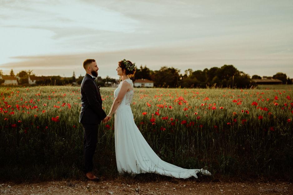 Couple de mariés devant un champs de coquelicots