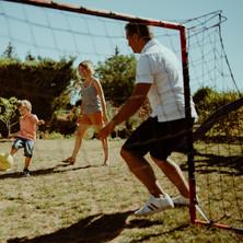 Photographe à Troyes, séance photo famille qui joue au foot dans le jardin