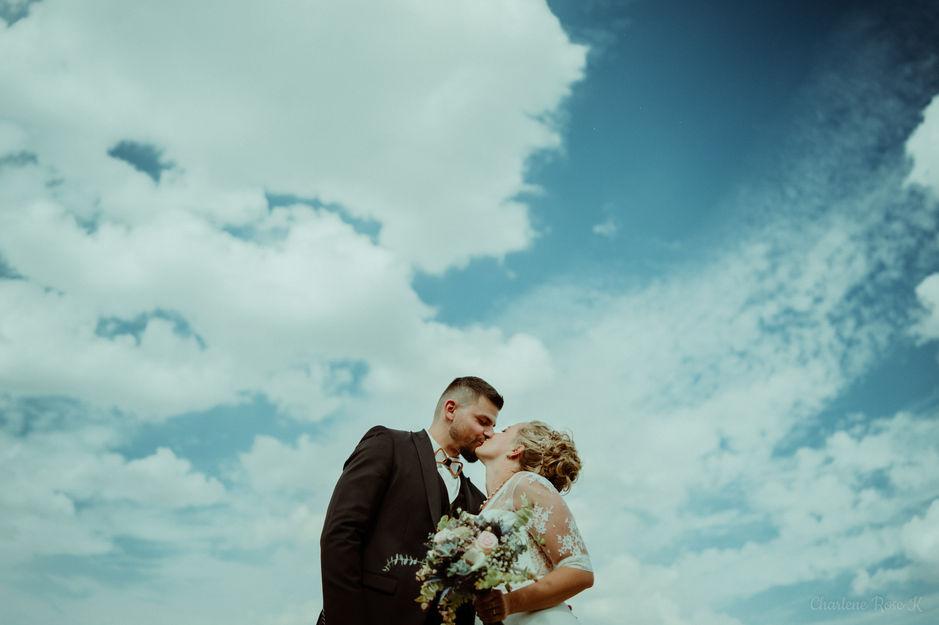 Photo en contre-plongée d'un couple de mariés qui s'embrasse