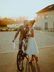 Jeunes mariés à vélo au coucher de soleil