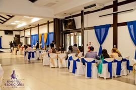 maneteleria sillas y mesas con lazos azul y dorado decoracion en paredes