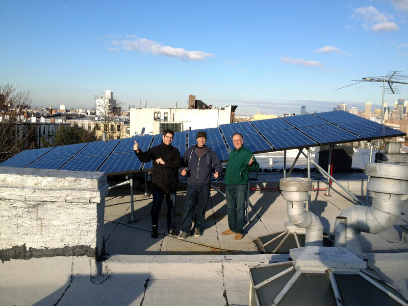 Men standing in front of solar panels on the roof of a Brooklyn home.