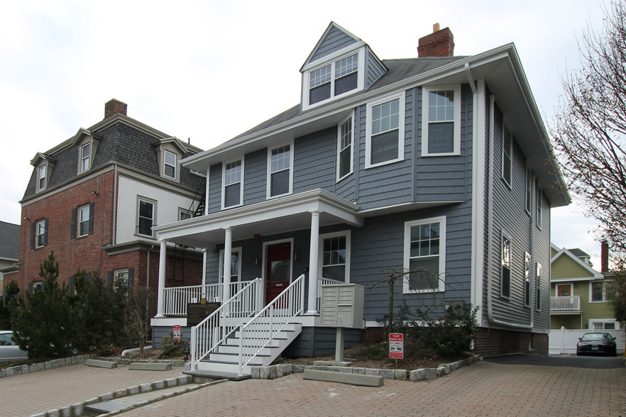 Photo of 35 S Angell Street, Providence, RI. Large two-story gray commercial building with customer parking.
