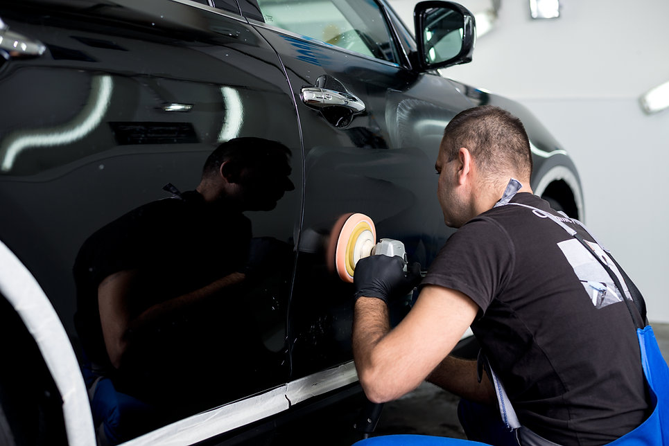 A person machine polishing the side panel of a car door.