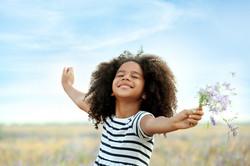 Happy little African American girl in the field.jpg