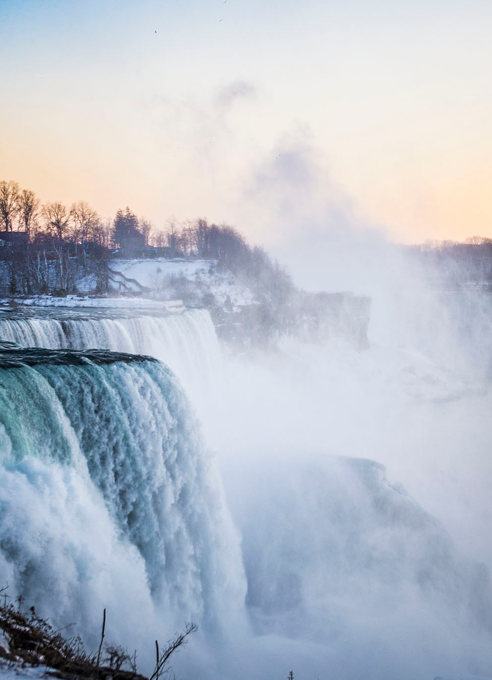 Mist over winter Niagara Falls at sunset