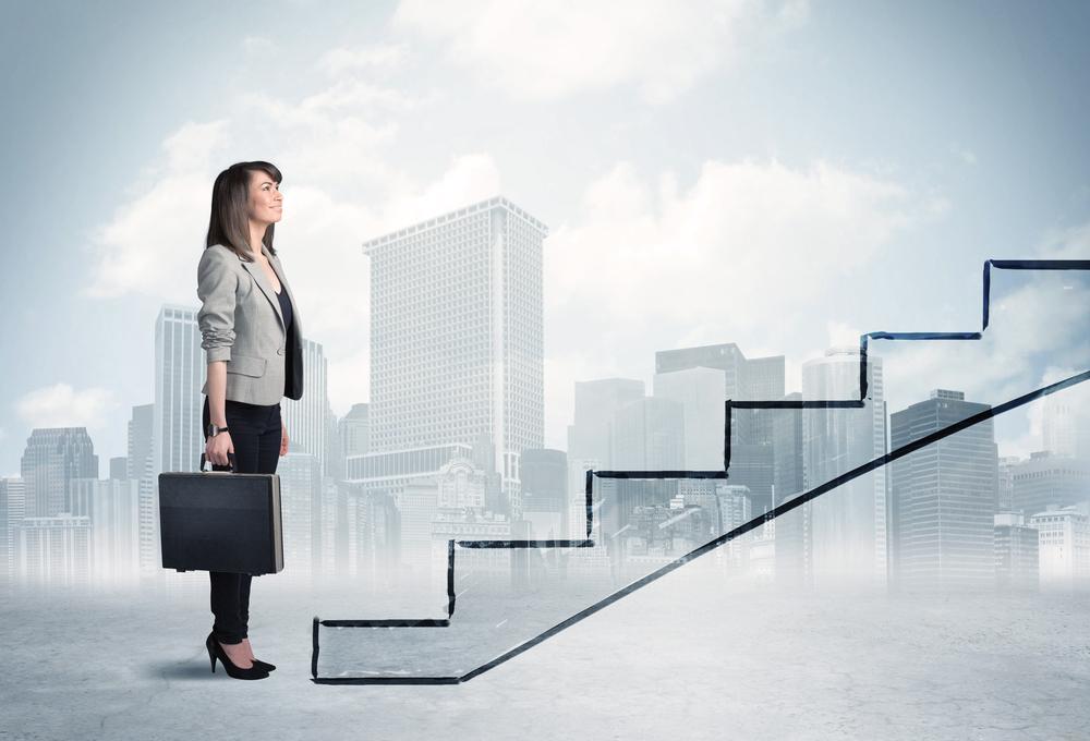Mulher diante de uma escada prestes a subir os degraus que irão alavancar sua carreira
