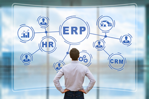 Homem diante de um quadro com um exemplo de ERP sistema integrado de gestão