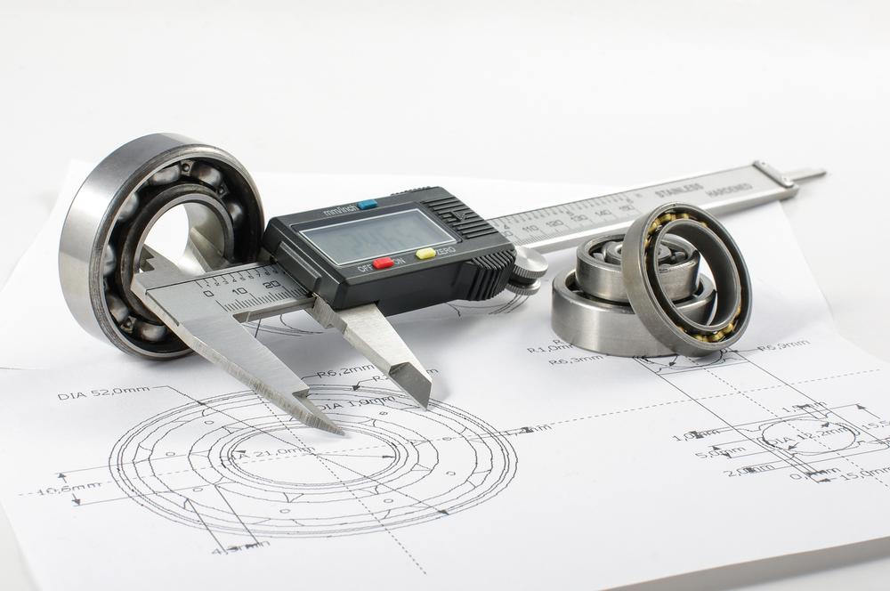 Imagem de um desenho técnico acompanhado de um paquímetro utilizado na metrologia