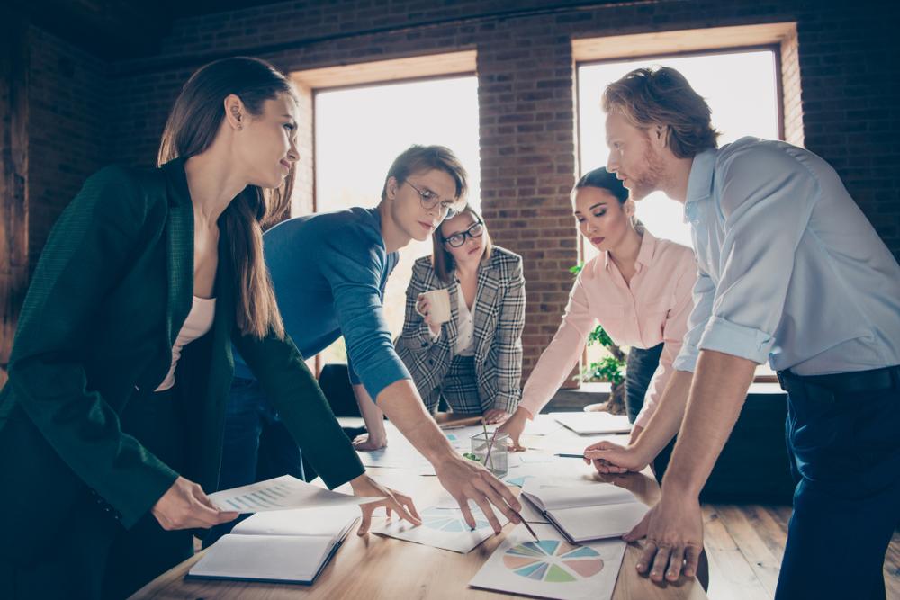Equipe reunida no trabalho colocando em prática suas habilidades técnicas desejadas pela empresa