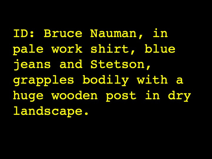 Bruce Nauman, in pale work shirt, blue jeans and Stetson, grapples bodily with a huge wooden post in dry landscape.