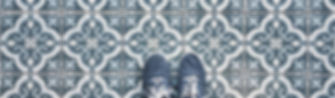 Selfie of feet with sneaker shoes on art pattern tiles floor, top view