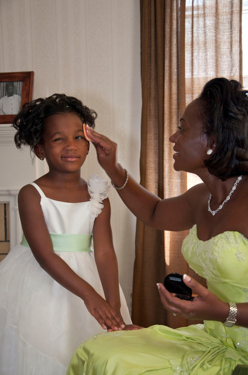 Young african american girl grimaces slighly as an older woman applies makeup to her face while getting ready for the wedding.