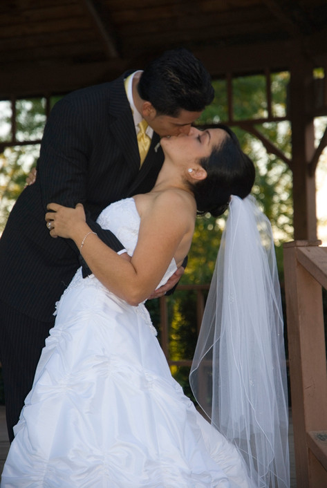 Domincan bride and groom kiss on the steps of a gazebo.