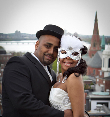 African american couple smile at the camera. He wears a hat and she wears a silver mask. The city of Boston is blurry in the background.