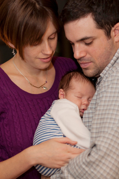 Husband and wife craddle their new born between them.