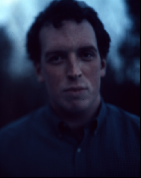 Blue toned blurry image of a serious young man.