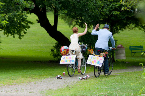 Bride and groom high-five as they ride away on their bikes. The bikes have baloons and just married signs.
