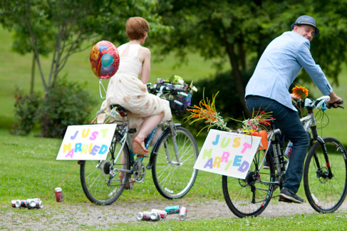 White bride and groom bike away in the park with Just Married signs and aluminum cans tied behind.