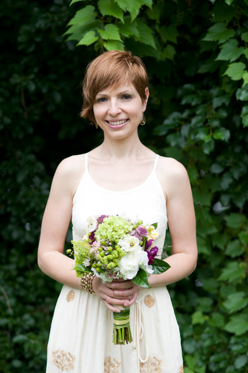 White bride poses with a serious smile while holding a bouqet of green, white purple flowers against a blurry backdrop of green leaves.