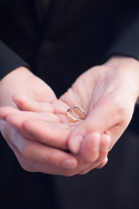 A close up a white man's hands cradling the wedding rings in his palm.