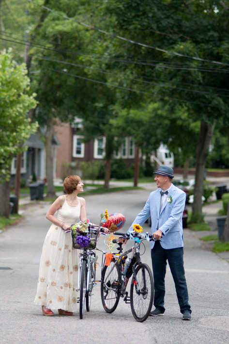White bride and groom pose with their wedding bikes, looking into each others eyes.
