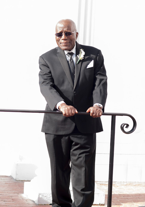 African american father of the bride stands proudly in the sun watching the wedding party arrive.