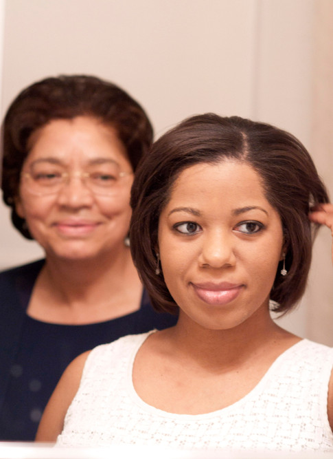 African american bride smiles in the mirror as her mother looks on behind her, looking proud.