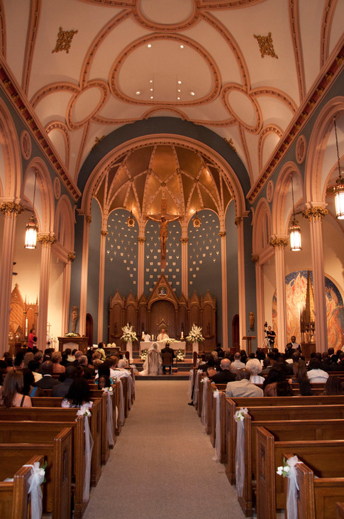 Wide shot of a cathlic church with lines of pews filled with guest. Bride and groom seated in the distance.