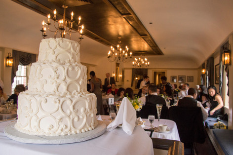 View of the banquet hall with a three story cream cake dominating the frame.