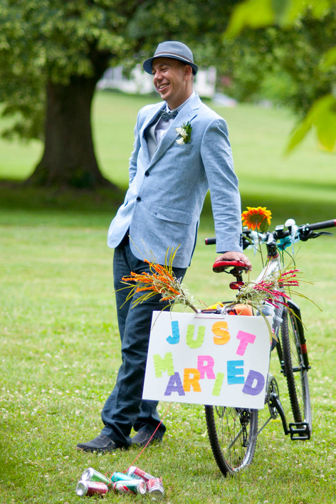 "White groom leans back smiling with one hand resting on wedding bike. Bike has ""Just Married"" signage."