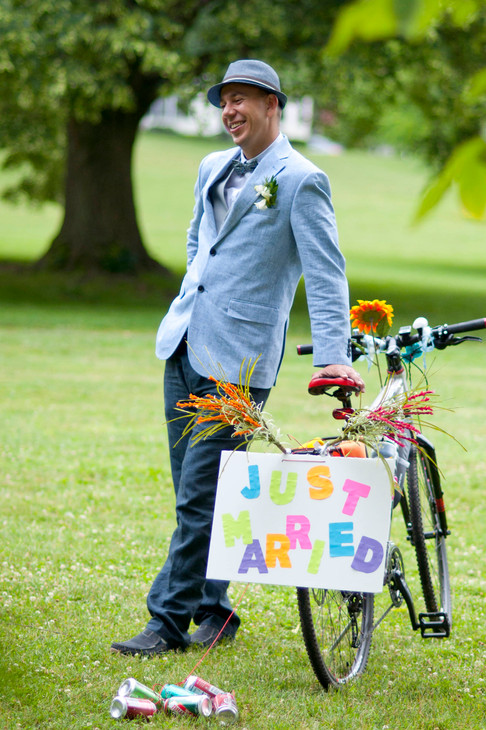 """White groom leans back smiling with one hand resting on wedding bike. Bike has """"Just Married"""" signage."""