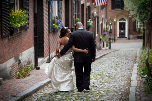 African american bride and groom stroll arm-in-arm down Acorn street in Boston's North End.