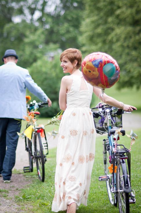 White bride glances backward smiling as she walks her bike down the path following her husband.