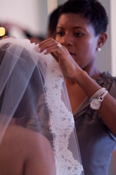 Bridesmaid adjusts the bride's veil in a close up shot.