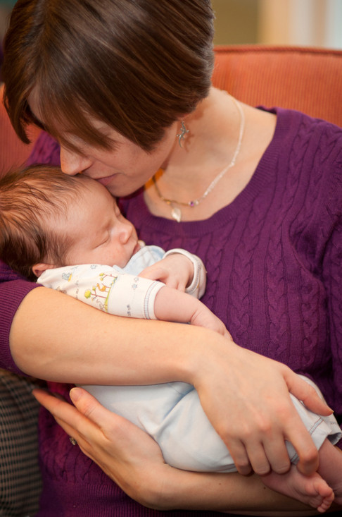 White mother gently kisses the top of her baby's head.